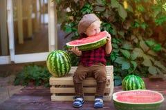 Un ragazzino con capelli biondi n l'estate un giorno soleggiato che si siede ad un gazebo con l'uva verde e che mangia un'anguria Fotografie Stock