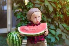 Un ragazzino con capelli biondi n l'estate un giorno soleggiato che si siede ad un gazebo con l'uva verde e che mangia un'anguria Fotografia Stock Libera da Diritti