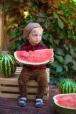 Un ragazzino con capelli biondi n l'estate un giorno soleggiato che si siede ad un gazebo con l'uva verde e che mangia un'anguria Immagini Stock