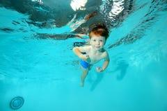 Un ragazzino con un sorriso sul suo fronte nuota underwater nello stagno su un fondo blu Immagine Stock Libera da Diritti