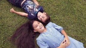 Un ragazzino con una ragazza divertendosi menzogne sull'erba archivi video