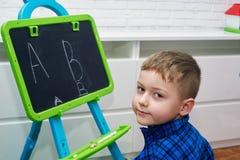 Un ragazzino disegna le lettere su una lavagna con gesso fotografia stock
