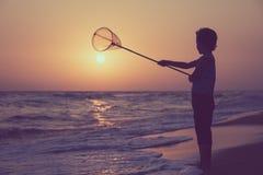 Un ragazzino felice che gioca sulla spiaggia al tempo di tramonto Immagine Stock