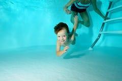 Un ragazzino impara tuffarsi underwater con sua madre nello stagno, esamina la macchina fotografica subacquea e sorride Fotografia Stock