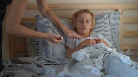 Un ragazzino malato in un letto La madre sfrega il petto del ragazzo con l'unguento con gli oli essenziali e le misure la sua tem archivi video