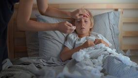 Un ragazzino malato in un letto Misure della madre la sua temperatura Concetto di influenza del bambino video d archivio