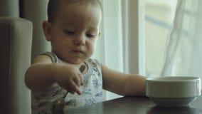 Un ragazzino mangia il porridge egli stesso 4k, archivi video