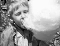 Un ragazzino mangia lo zucchero filato dolce delizioso nel parco, amore immagini stock
