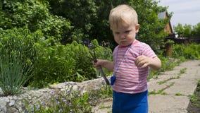 Un ragazzino nel giardino da imparare utilizzare l'attrezzatura di giardino fotografia stock libera da diritti
