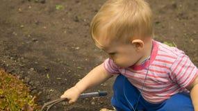 Un ragazzino nel giardino da imparare utilizzare l'attrezzatura di giardino immagine stock libera da diritti
