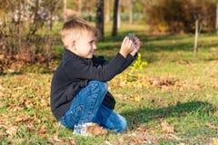 Un ragazzino prende le immagini sul telefono nel parco un giorno soleggiato fotografia stock libera da diritti
