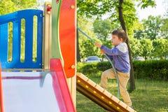Un ragazzino scala la collina del ` s dei bambini che tiene la corda Giochi da bambini su un campo da giuoco del ` s del bambino Immagine Stock Libera da Diritti