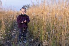 Un ragazzino si leva in piedi in mezzo dell'erba alta. Fotografia Stock Libera da Diritti