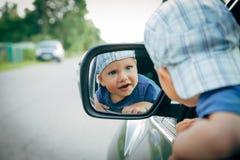 Un ragazzino si siede dietro la ruota e lo sguardo nello specchio laterale immagine stock libera da diritti