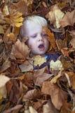 Un ragazzino si trova nel mucchio della foglia Fotografia Stock