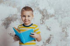 Un ragazzino ? sorridente e tenente un libro aperto blu che posa davanti ad un muro di cemento grigio fotografia stock