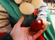 Un ragazzino sta giocando con un uovo di Pasqua rosso in sue mani fotografie stock libere da diritti