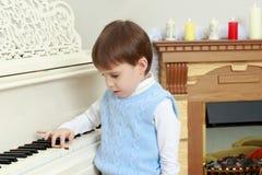 Un ragazzino sta sedendosi al piano Fotografia Stock