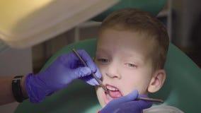 Un ragazzino sta sedendosi nella sedia del ` s del dentista con la sua bocca aperta Il dentista controlla i denti del ` s del bam video d archivio