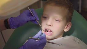 Un ragazzino sta sedendosi nella sedia del ` s del dentista con la sua bocca aperta Il dentista controlla i denti del ` s del bam archivi video