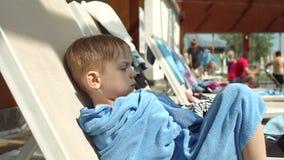 Un ragazzino sta sedendosi su una chaise-lounge del sole dallo stagno si è avvolto in un asciugamano video d archivio