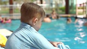 Un ragazzino sta sedendosi su una chaise-lounge del sole dallo stagno si è avvolto in un asciugamano archivi video