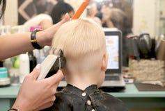 Un ragazzino sta tagliando un parrucchiere nel salone Il bambino sta guardando un fumetto Schermo verde su un computer portatile  fotografia stock libera da diritti