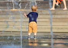 Un ragazzino sveglio che gioca in una fontana nel giorno di estate caldo Immagine Stock Libera da Diritti