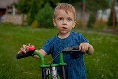 Un ragazzino sveglio con una bicicletta vicino alla casa, uno sport per i bambini, una famiglia attiva sulla via Fotografia Stock