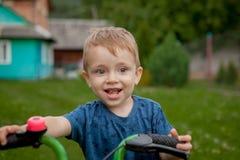Un ragazzino sveglio con una bicicletta vicino alla casa, uno sport per i bambini, una famiglia attiva sulla via Fotografie Stock Libere da Diritti