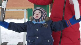 Un ragazzino sveglio e una giovane madre sono impegnati in attrezzatura all'aperto di esercizio ` s duro affinchè un bambino ragg archivi video