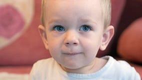 Un ragazzino sveglio mangia il porridge con i pezzi di carne ad una tavola del ` s dei bambini Arredamento domestico archivi video