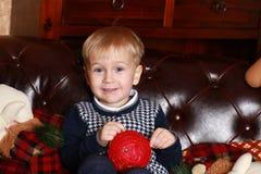 Un ragazzino in un maglione che si siede su un sofà marrone Fotografia Stock Libera da Diritti