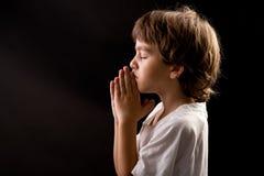 Un ragazzino in una preghiera pacifica spiritosa di momento Immagini Stock