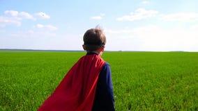 Un ragazzino vestito in un costume del superman funziona attraverso un campo verde un giorno soleggiato archivi video