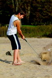 Un ragazzo 10 colpisce una sfera di golf alla spiaggia Immagine Stock