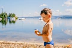 Un ragazzo abbronzato di tre anni in costume da bagno gioca sul lago di estate, le vacanze estive, infanzia immagini stock