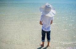 Un ragazzo al mare Maglietta bianca, pantaloni scuri e cappello A piedi nudi sulla sabbia bianca e sulla chiara acqua Isolato su  Immagini Stock