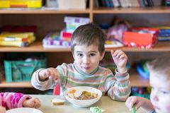 Un ragazzo all'età di 5 anni che mangia minestra nell'asilo Immagine Stock Libera da Diritti