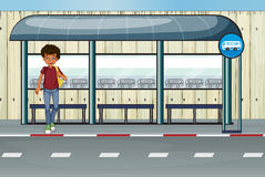 Un ragazzo alla fermata dell'autobus Immagini Stock Libere da Diritti
