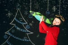 Un ragazzo bello con un aereo di legno del giocattolo, un retro casco su un fondo con un albero dipinto Immagini Stock