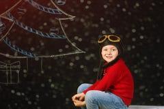 Un ragazzo bello con un aereo di legno del giocattolo, un retro casco su un fondo con un albero dipinto Immagine Stock