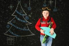 Un ragazzo bello con un aereo di legno del giocattolo, un retro casco su un fondo con un albero dipinto Fotografie Stock