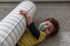 Un ragazzo biondo sveglio gioca e gode di sul tappeto nella sua camera da letto immagini stock