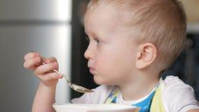 Un ragazzo biondo sveglio mangia un porridge con un cucchiaio da un piatto della casa Primo piano stock footage
