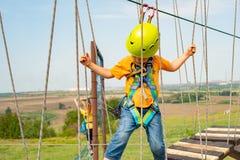 Un ragazzo in un casco giallo supera un ostacolo sulla cabina di funivia in un parco estremo immagine stock