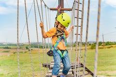 Un ragazzo in un casco giallo supera un ostacolo sulla cabina di funivia in un parco estremo fotografia stock libera da diritti