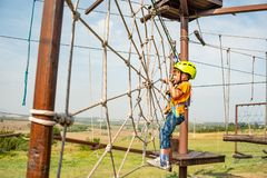 Un ragazzo in un casco giallo supera un ostacolo sulla cabina di funivia in un parco estremo fotografia stock