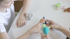 Un ragazzo caucasico che gioca con lo psicologo, ruoli differenti dello psicoterapeuta usando i burattini del dito, giocattoli pe video d archivio