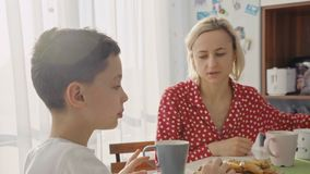 Un ragazzo caucasico sveglio adorabile sta mangiando il biscotto accanto alla sua giovane madre con capelli biondi video d archivio
